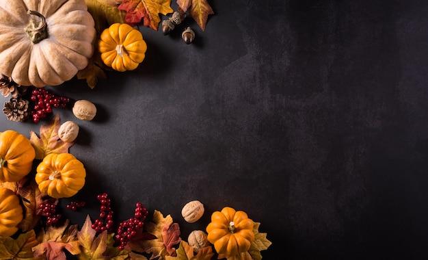Composição de outono flores de algodão de abóbora e folhas de outono em pedra escura