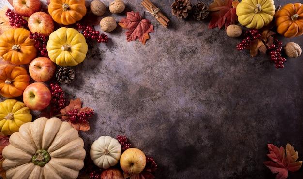 Composição de outono folhas de outono de abóbora e maçã em fundo de pedra escura