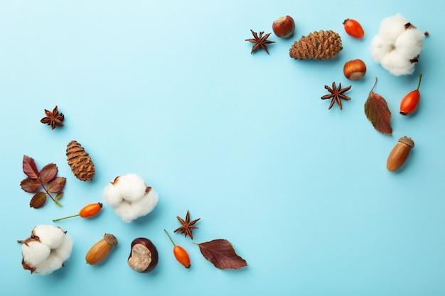 Composição de outono. folhas secas, flores, bagas, sobre fundo azul. conceito do dia de ação de graças. camada plana, vista superior, espaço de cópia Foto Premium