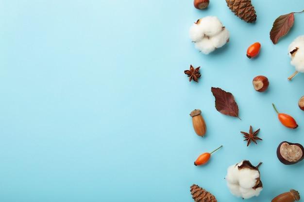 Composição de outono. folhas secas, flores, bagas, sobre fundo azul. conceito do dia de ação de graças. camada plana, vista superior, espaço de cópia