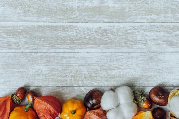 Composição de outono. fronteira de castanhas, pinhas, physalis, bolota em fundo de madeira. postura plana, copie o espaço