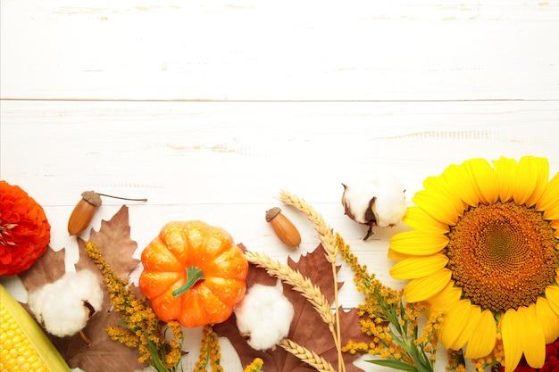 Composição de outono. moldura feita de flores frescas em fundo branco de madeira. camada plana, vista superior, espaço de cópia. dia de ação de graças