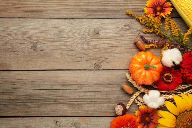 Composição de outono. moldura feita de flores frescas em fundo cinza de madeira. camada plana, vista superior, espaço de cópia. dia de ação de graças