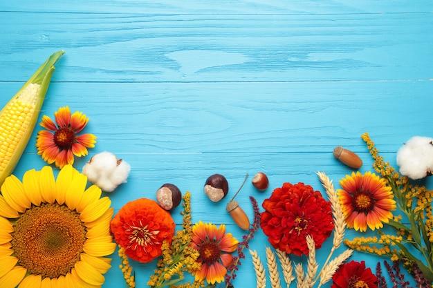 Composição de outono. moldura feita de flores frescas sobre fundo azul de madeira. camada plana, vista superior, espaço de cópia. dia de ação de graças
