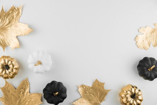 Composição de outono. moldura feita de folhas douradas de outono e abóboras decorativas