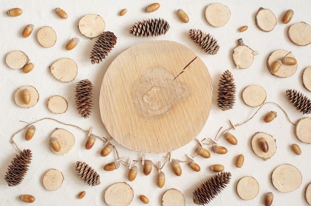Composição de outono, moldura feita de pinhas, bolotas e pequenos tocos de madeira.