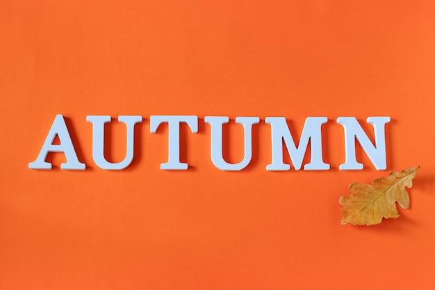 Composição de outono. palavra outono de letras brancas e folhas de carvalho amarelo brilhante