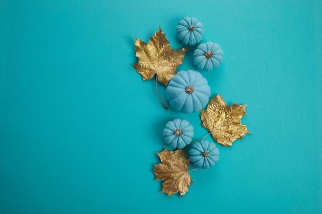 Composição de outono plana de vista superior. moldura feita de abóboras de cor água e folhas secas de ouro em fundo água. colher cartões de aniversário do dia das bruxas para o dia de ação de graças