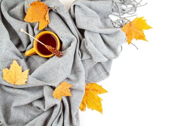 Composição de outono plana leiga com uma xícara de chá e um cachecol de lã quente