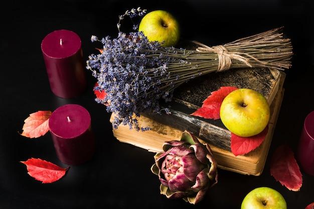 Composição de outono quente. livros antigos, velas, maçãs verdes, alfazema seca, alcachofra e folhas vermelhas de outono criando um ambiente aconchegante e romântico.