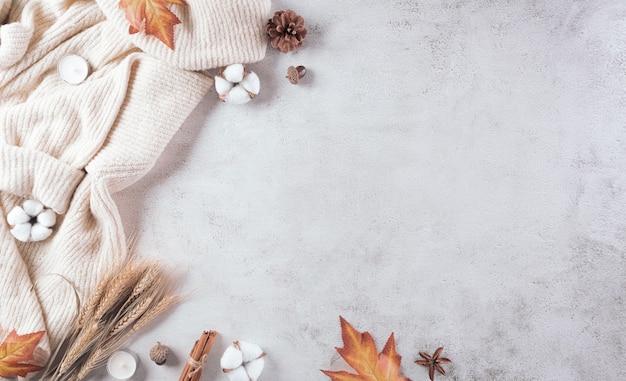 Composição de outono uma xícara de café flores de algodão folhas de outono e camisola em pedra
