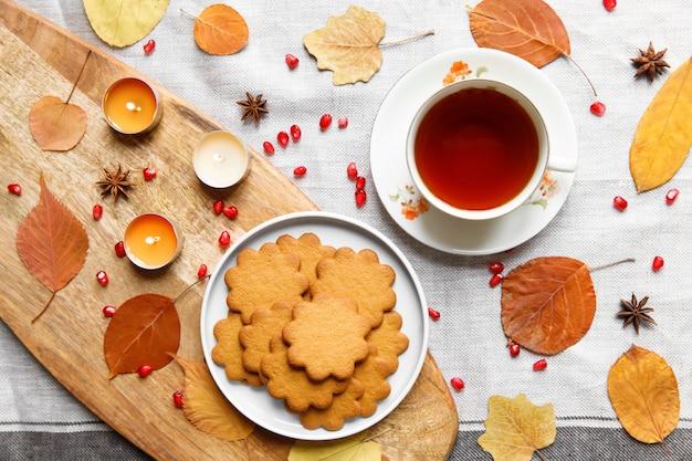 Composição de outono. xícara de chá quente, biscoito de gengibre, velas acesas, folhas amarelas caídas, sementes de romã, anis em uma toalha de mesa de linho