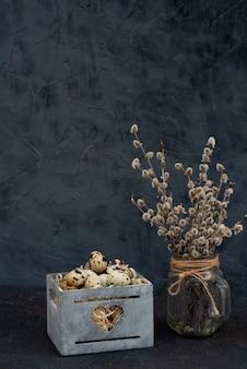 Composição de ovo de codorna em uma caixa de madeira de ramos de salgueiro em um vaso
