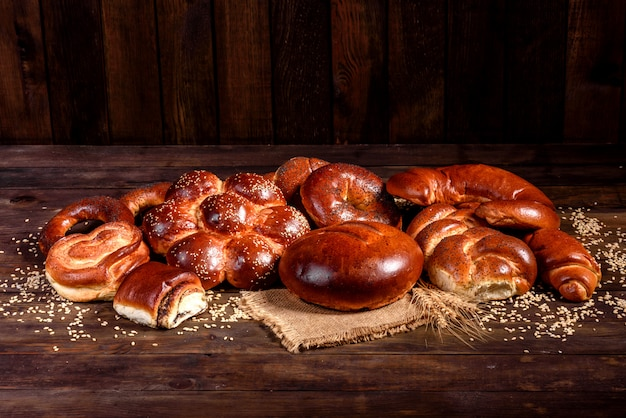 Composição de pães doces cozidos frescos com papoula e geléia. cozimento doce, disposto como uma composição em uma mesa de madeira