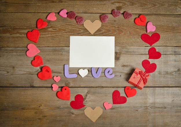Composição de palavra amor com cartão vazio para texto na superfície da placa de madeira e corações