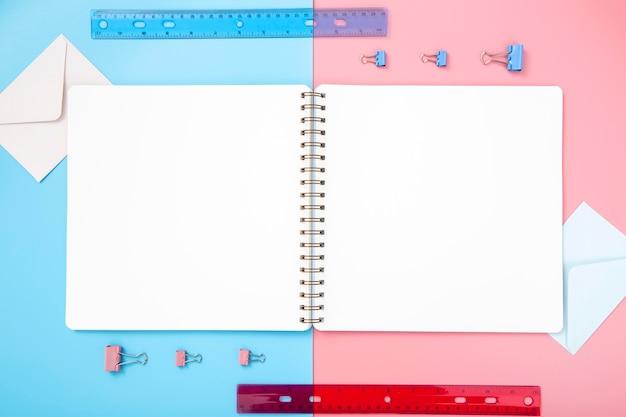 Composição de papelaria vista superior em fundo bicolor com caderno vazio