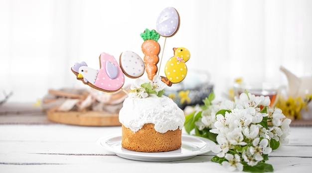 Composição de páscoa com bolo de páscoa lindamente decorado e flores da primavera. o conceito de preparação para o feriado da páscoa.