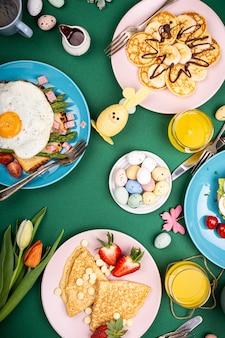 Composição de páscoa com café da manhã plano deitado com bagels de ovos mexidos, tulipas, panquecas, torradas de pão com ovo frito e aspargos verdes, ovos de codorna coloridos. vista do topo