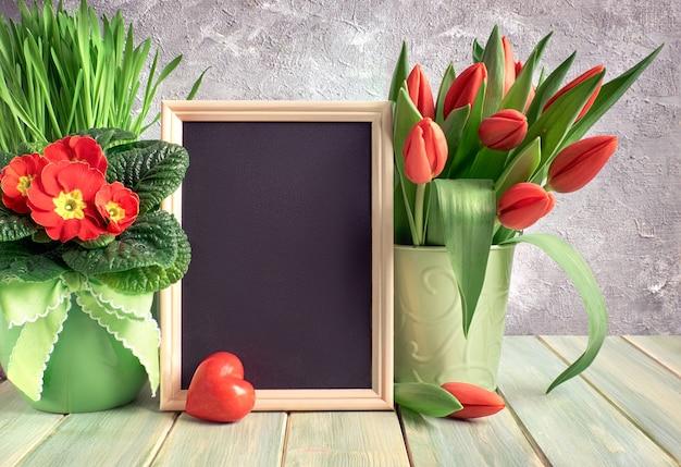 Composição de páscoa com coração de pedra vermelha e flores da primavera vermelhas em madeira rústica, cópia espaço