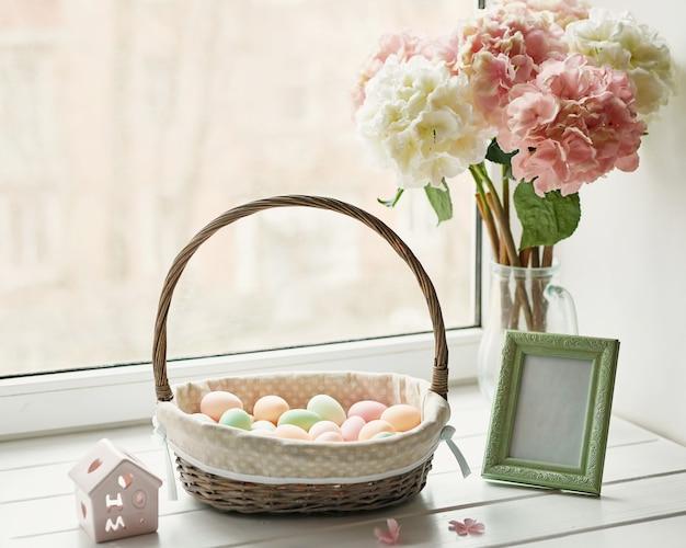 Composição de páscoa com hortênsias rosa e brancas em vaso e ovos em uma cesta de vime