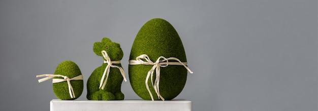 Composição de páscoa com lebre e ovos de cor verde sobre fundo cinza, lugar para texto