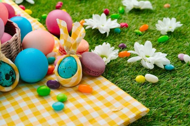 Composição de páscoa com ovos coloridos e doces brilhantes na toalha de mesa amarela