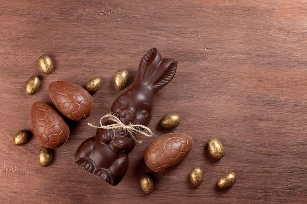 Composição de páscoa com ovos de chocolate e coelho em fundo de madeira