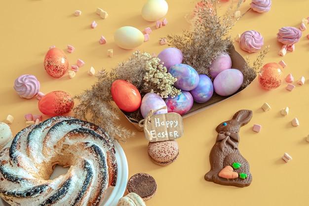 Composição de páscoa com ovos e cupcake no colorido.