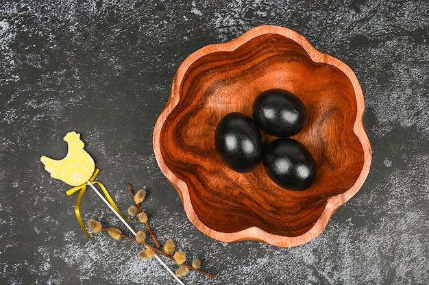 Composição de páscoa com ovos pretos, salgueiro e chiken de madeira.