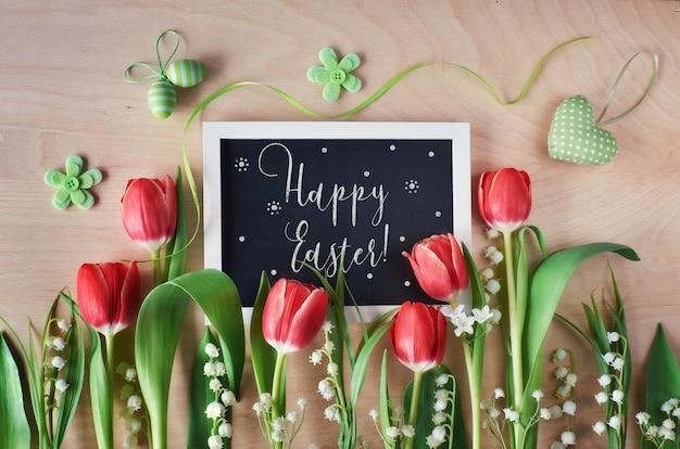 Composição de páscoa com quadro negro emoldurado com flores da primavera, tulipas e lírio do vale, texto