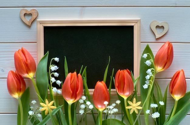 Composição de páscoa com quadro negro emoldurado com flores da primavera, tulipas e lírio