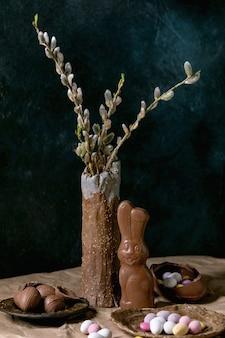 Composição de páscoa com ramos de flor de salgueiro em vaso de cerâmica, coelho de chocolate tradicional, ovos e doces na mesa com papel artesanal amassado