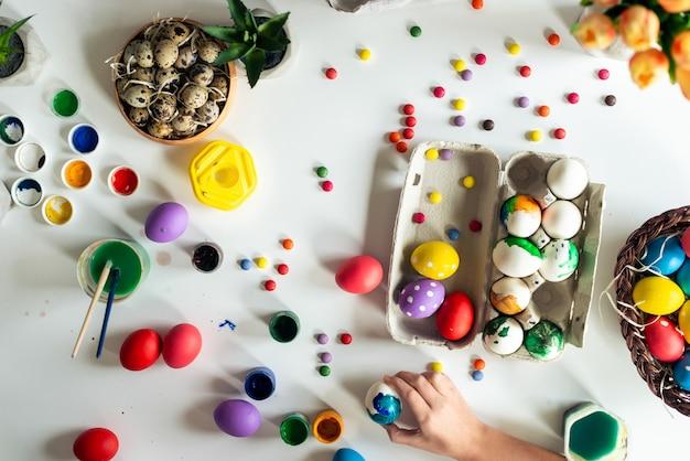 Composição de páscoa com tintas coloridas e ovos deite na mesa. vista do topo