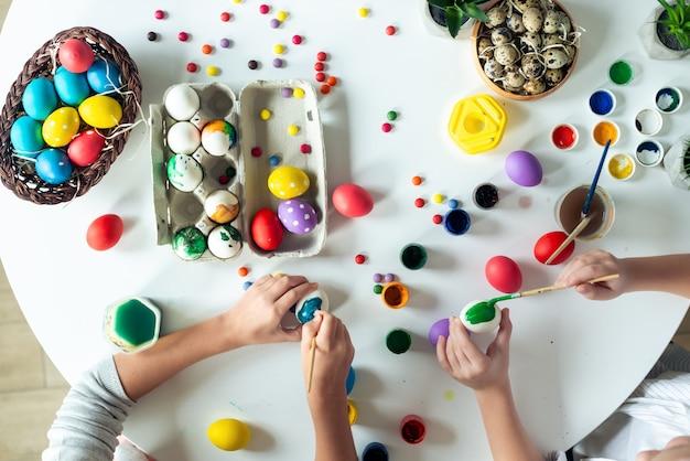 Composição de páscoa com tintas coloridas e ovos deite na mesa. vista superior as mãos das crianças estão pintando um ovo