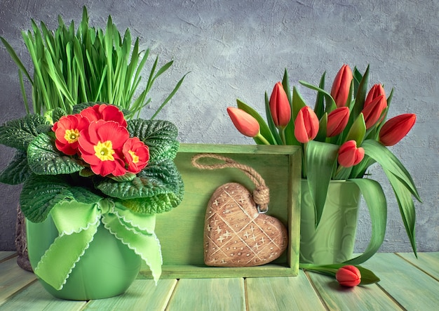 Composição de páscoa com tulipas vermelhas e flores de prímula, caixa verde e coração de madeira
