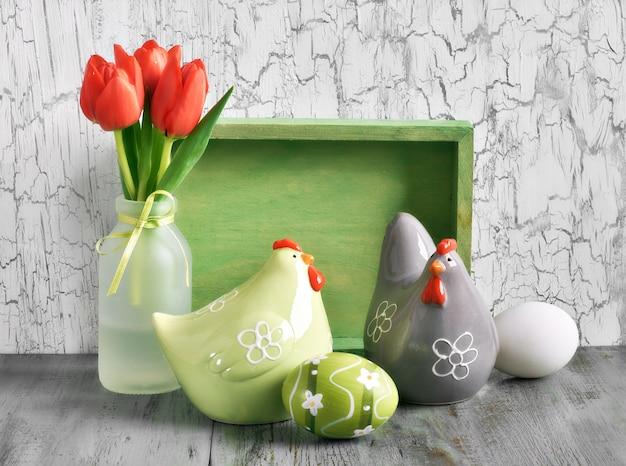 Composição de páscoa com tulipas vermelhas, galinhas de cerâmica e ovos de páscoa