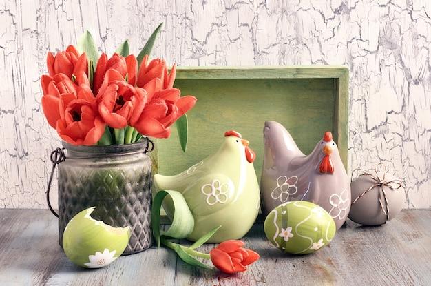Composição de páscoa com tulipas vermelhas; galinhas de cerâmicas e ovos de páscoa na madeira