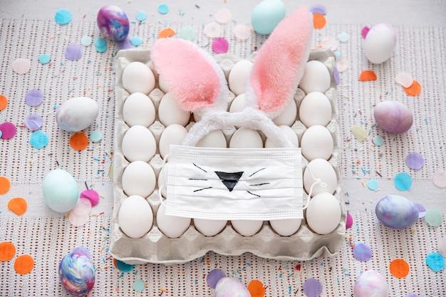 Composição de páscoa com uma bandeja de ovos, uma máscara médica com um rosto pintado de coelhinho da páscoa e orelhas entre confetes close-up