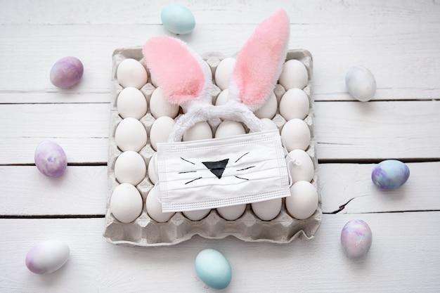 Composição de páscoa com uma bandeja de ovos, uma máscara médica com um rosto pintado de coelhinho da páscoa e orelhas fecham-se.