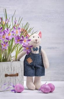 Composição de páscoa de açafrão, o brinquedo de coelho e ovos violeta