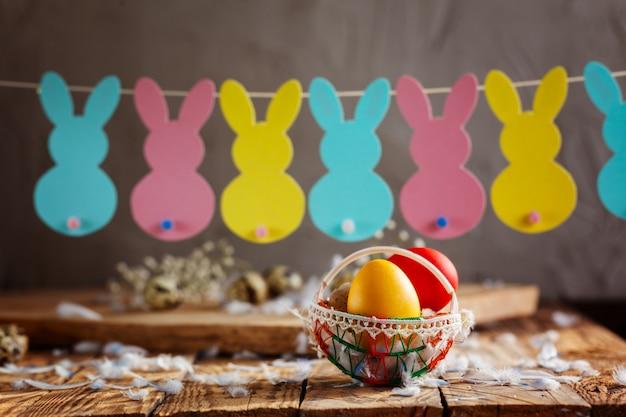 Composição de páscoa de ovos coloridos de páscoa na cesta e com guirlanda de coelho.
