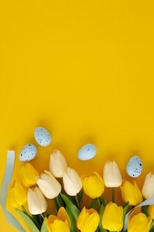 Composição de páscoa feita com tulipas e ovos pascais em fundo amarelo com espaço de cópia