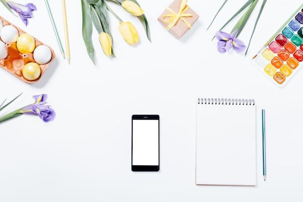Composição de páscoa: flores, telefone inteligente, ovos pintados, aquarelas e caderno