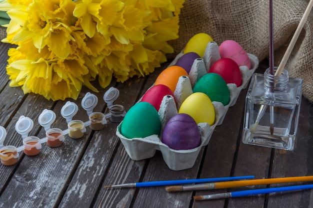 Composição de páscoa: na mesa narcisos amarelos, ovos, tintas, pincéis