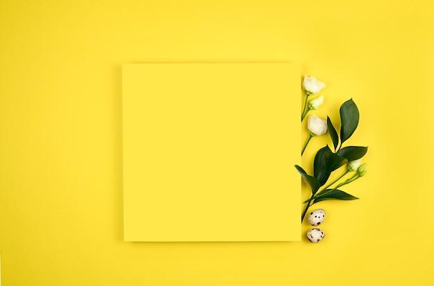 Composição de páscoa. ovos de páscoa, flores, papel em branco sobre fundo amarelo.