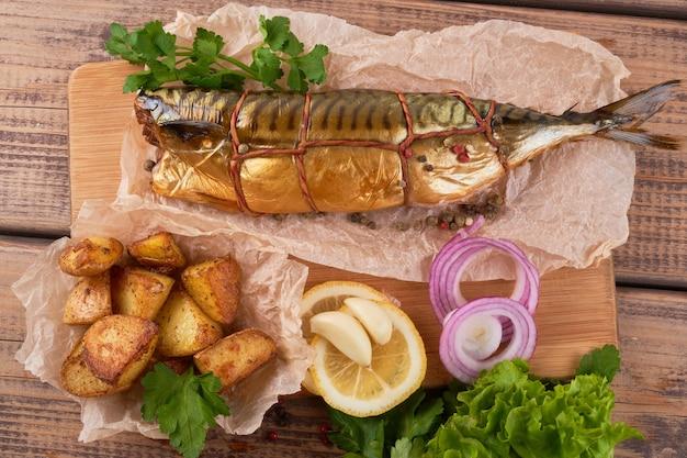 Composição de peixes de cavala defumada com guarnição de batatas e cebolas verdes e limão servidos em uma placa de madeira vista de cima