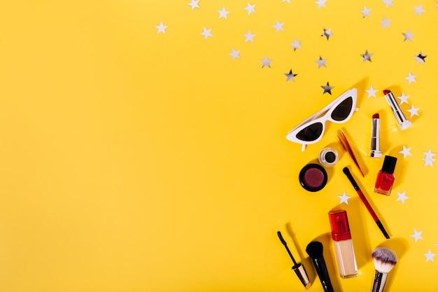 Composição de pincéis de maquiagem, base tonal, delineador, batom, rímel e óculos de sol elegantes na parede laranja com estrelas prateadas