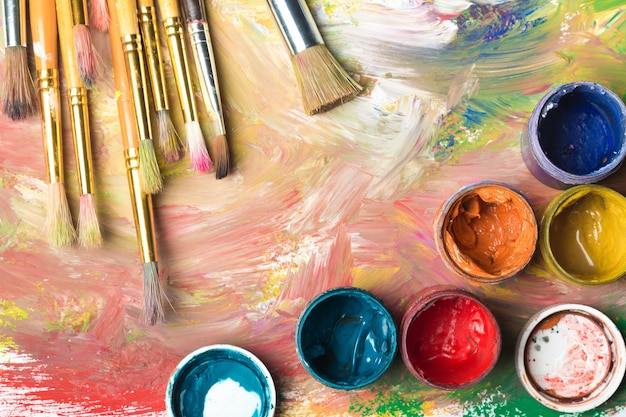 Composição de pincéis sujos em fundo colorido