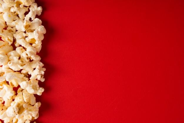 Composição de pipoca sobre fundo vermelho, com espaço de cópia
