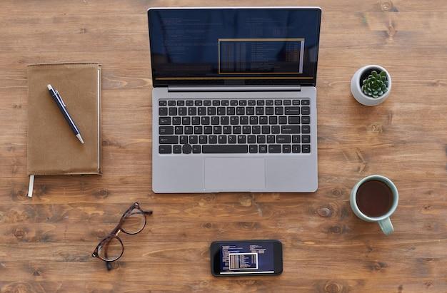 Composição de plano de fundo de vista de cima para baixo do laptop e smartphone com código de computador em mesa de madeira texturizada no escritório